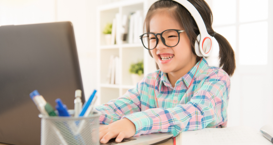 Young girl with headphones on a computer