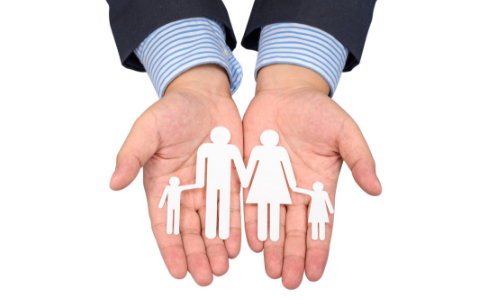 Hands holding a paper cut out family