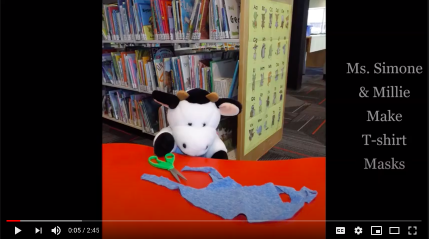Stuffed animal cow sitting at a desk with a t-shirt and scissors