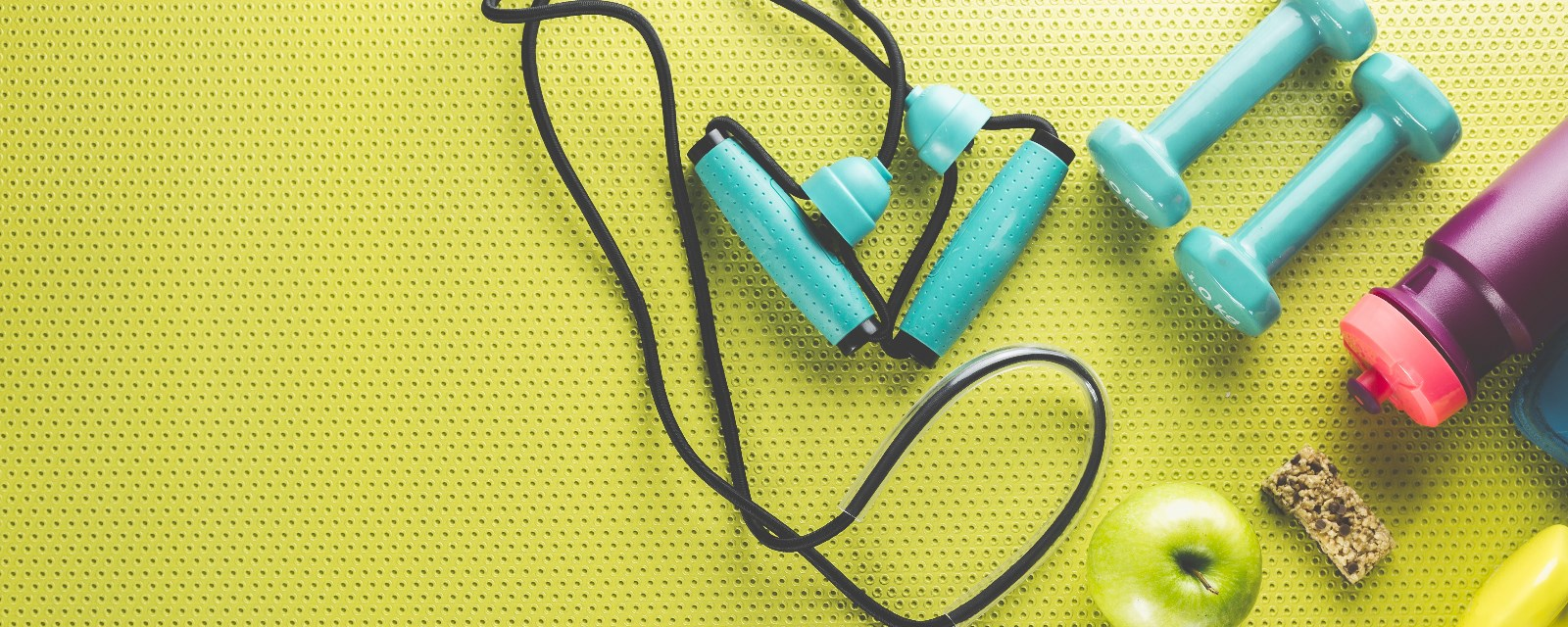 A water bottle, set of weights and jump rope laying on a bright fitness mat
