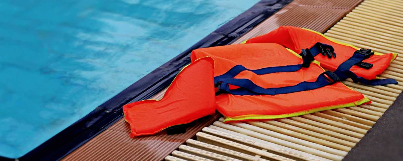 An orange life jacket laying on the edge of the pool deck
