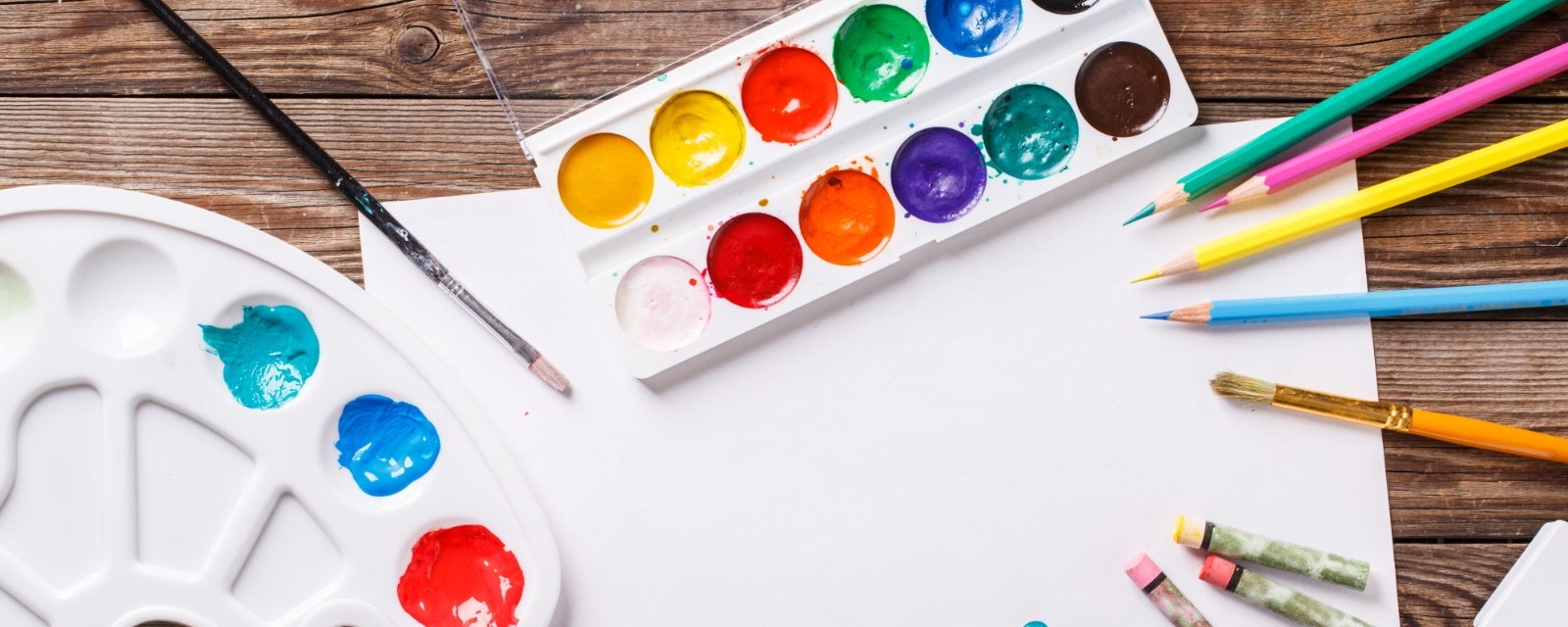 art artists palette, paint brushes and paint with a blank piece of paper