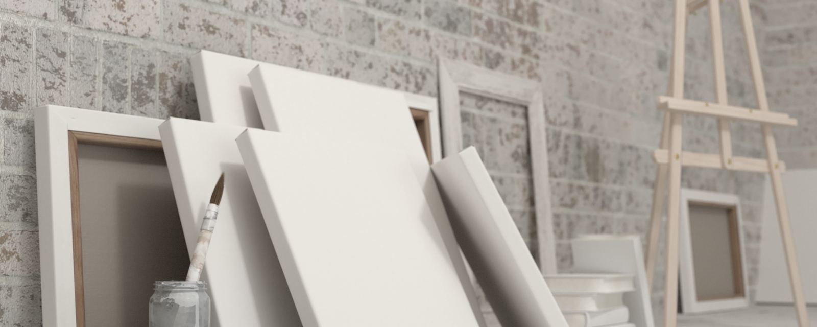 blank artist canvases and an easel leaning against a wall