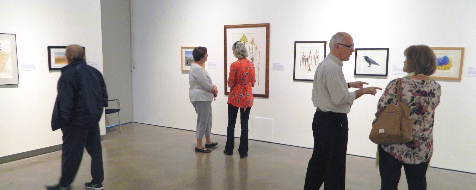 visitors looking at and discussing artwork on the walls at the Grimsby Public Art Gallery